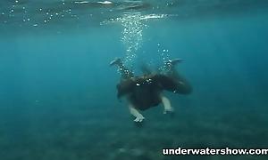Julia is swimming underwater nude in strong the ocean