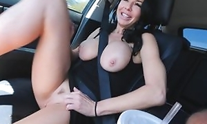 Raven haired adult in high heels masturbates in the car