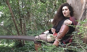 Curly-haired call-girl in egotistical boots masturbates outdoors
