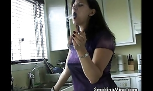 Sexy MILF makes herself some coffee while smokin'